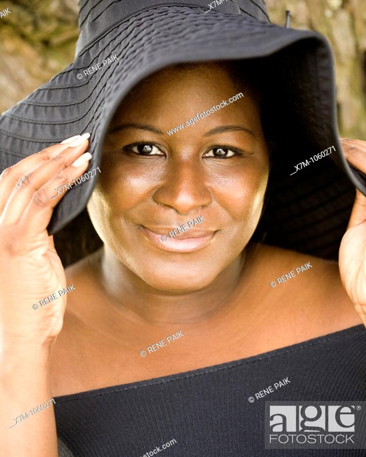 Stock Photo: A black woman wears a hat for sun protection.