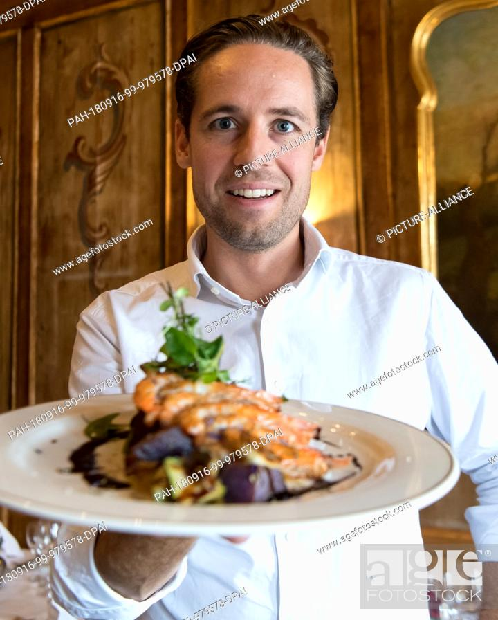 Stock Photo: 14 September 2018, Bavaria, Langenpreising: Fabian Riedel, Managing Director of Crusta Nova, holds a plate with a prawn skewer (Pacific White Shrimp) in his.