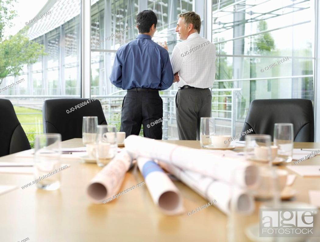 Stock Photo: Businessmen looking out conference room window.