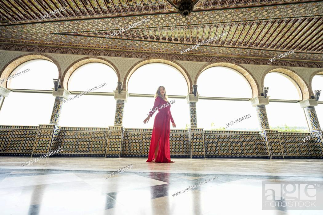 Stock Photo: Woman dancing in a red dress in the halls of the Arab palace.