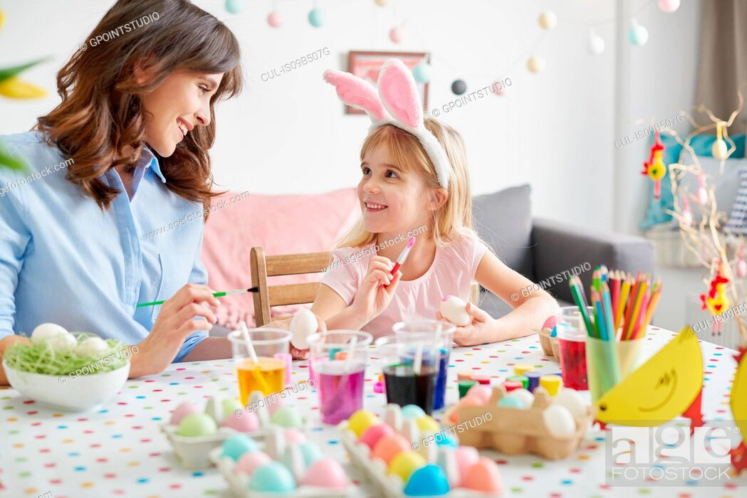 Stock Photo: Girl and mother painting easter eggs at table.