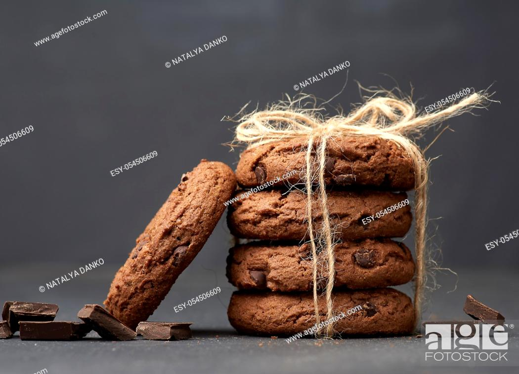 Stock Photo: stack of round chocolate chip cookies tied with a rope on a black board, delicious dessert.