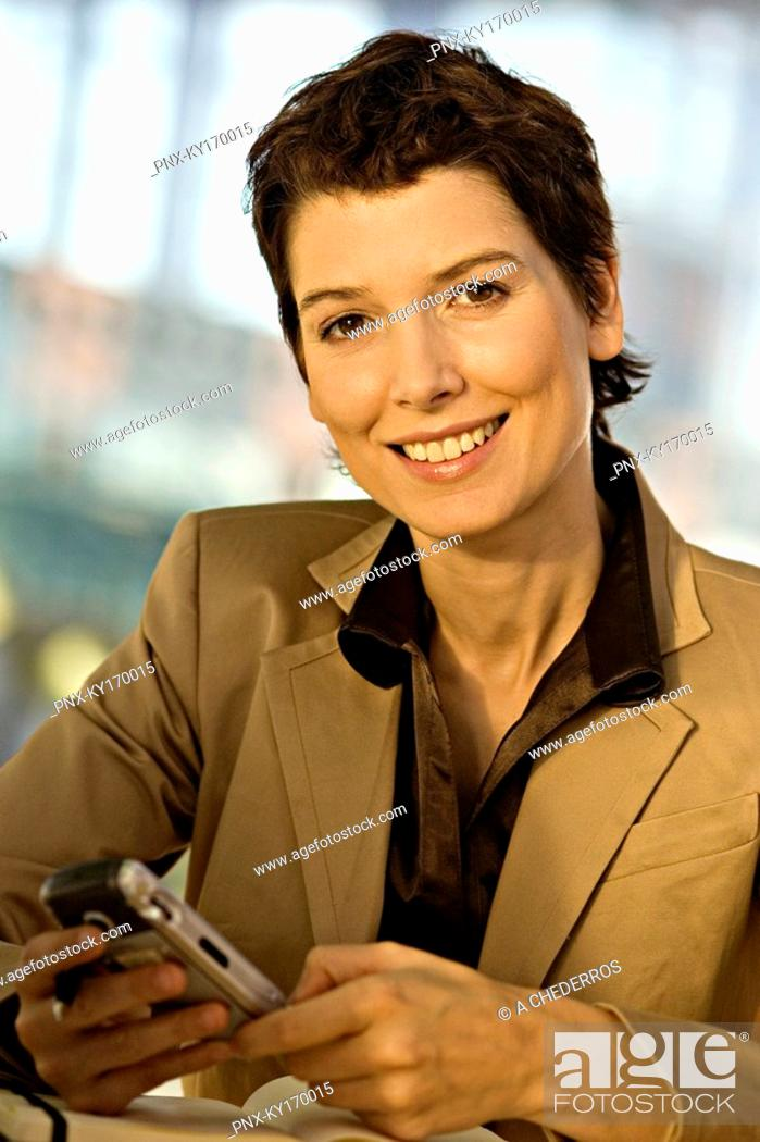 Stock Photo: Portrait of a businesswoman operating a mobile phone and smiling.