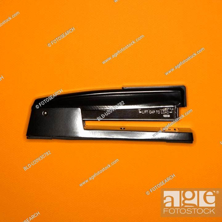 Stock Photo: Black stapler on orange background.
