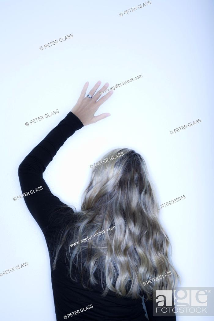 Stock Photo: Young blonde woman, with her arm raised, facing a wall.