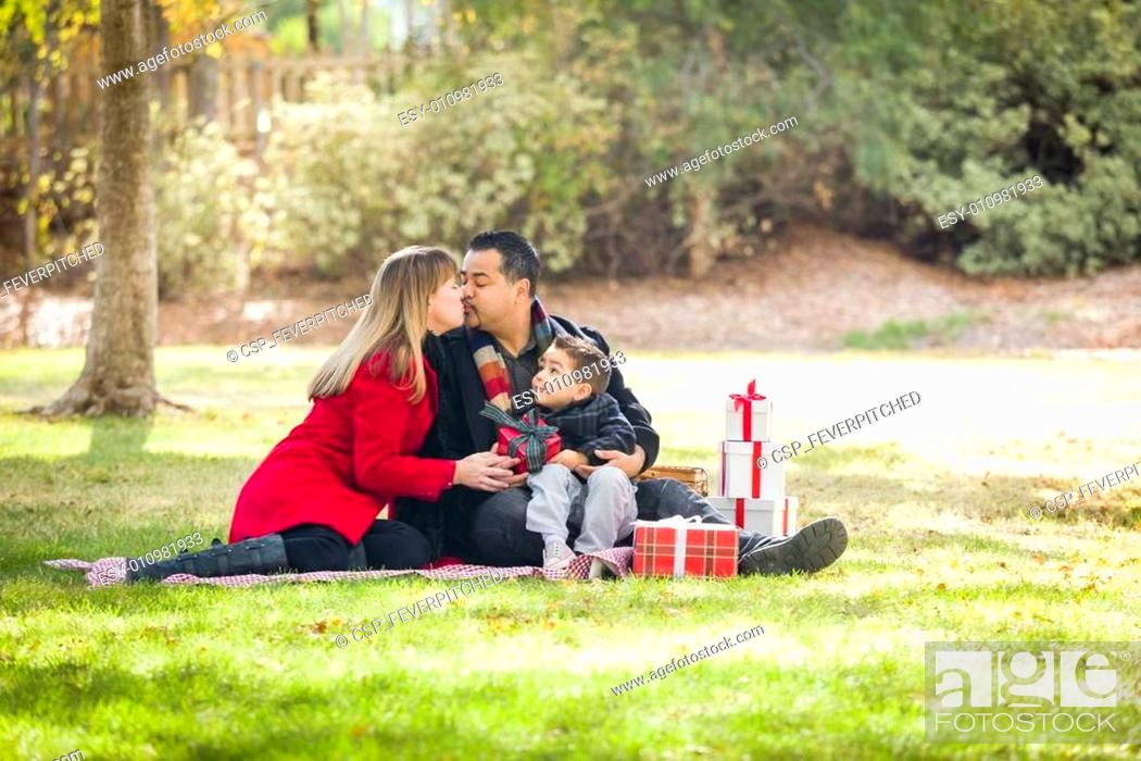 Stock Photo: Mixed Race Family Enjoying Christmas Gifts in the Park Together.