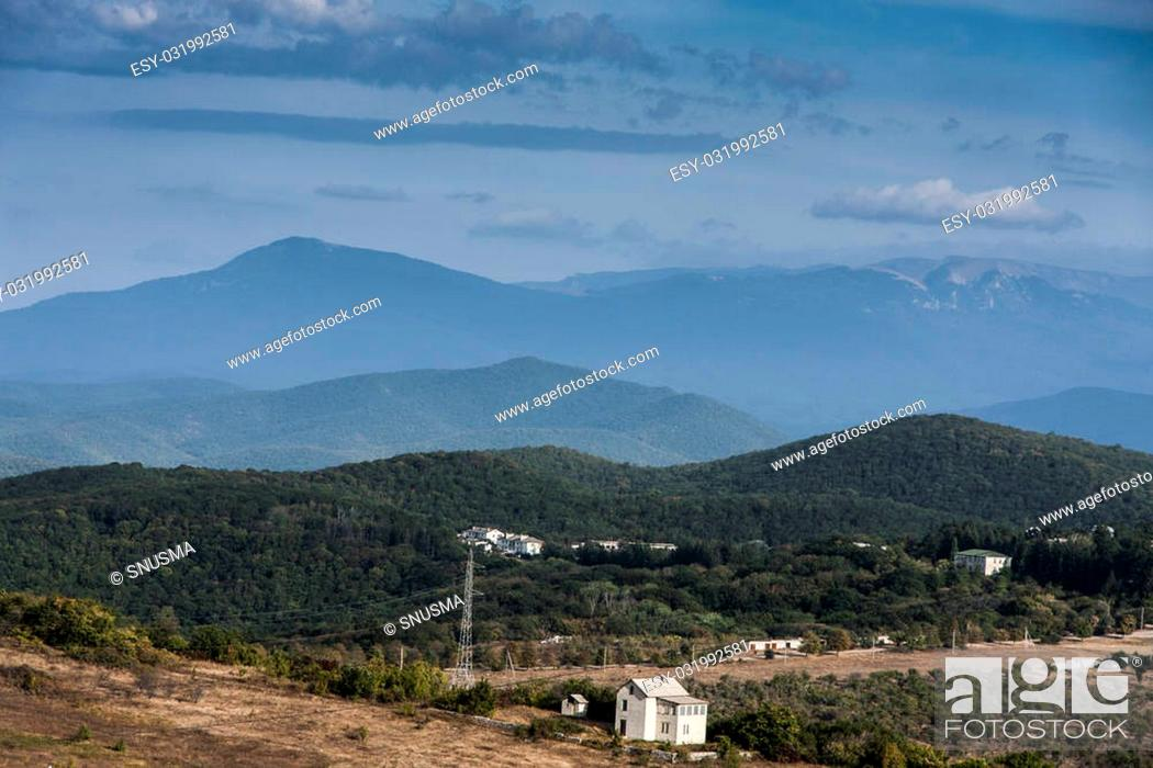 Stock Photo: several houses in a small town surrounded by mountains.