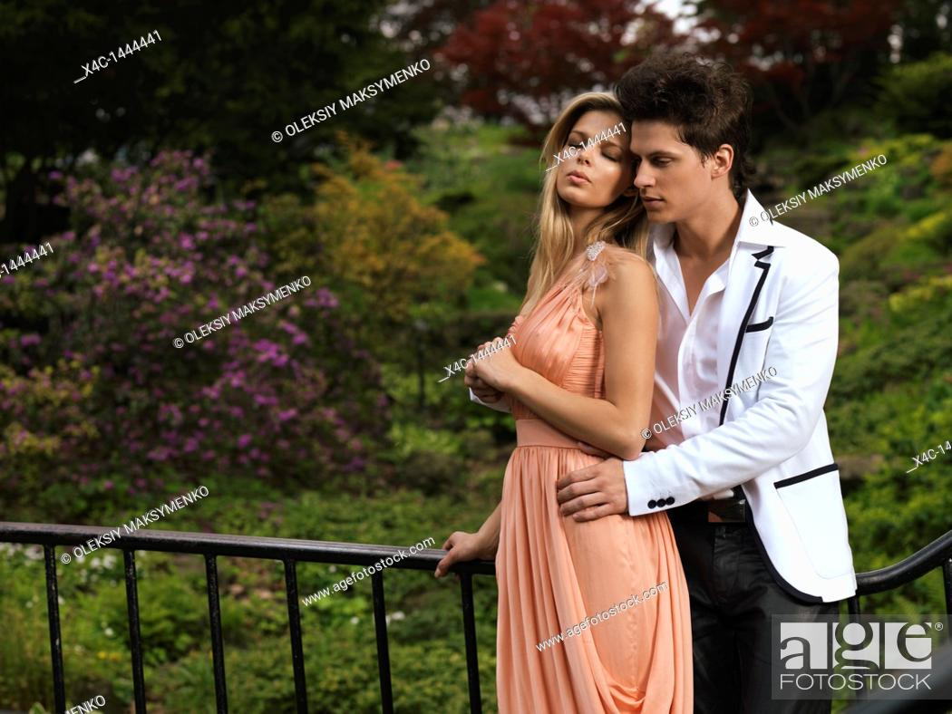 Stock Photo: Young romantic couple standing on a bridge in a park  Springtime scenic.