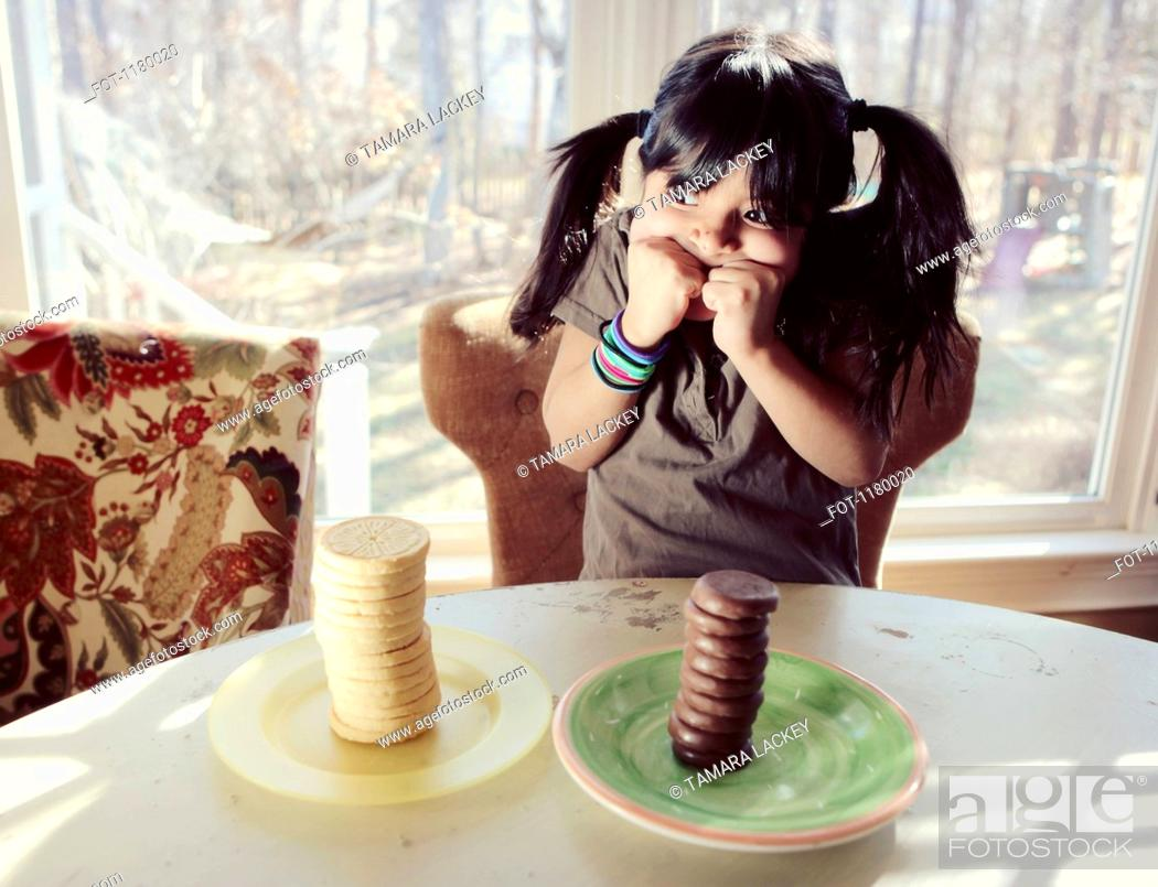 Stock Photo: A girl trying to decide between two stacks of vanilla and chocolate cookies.