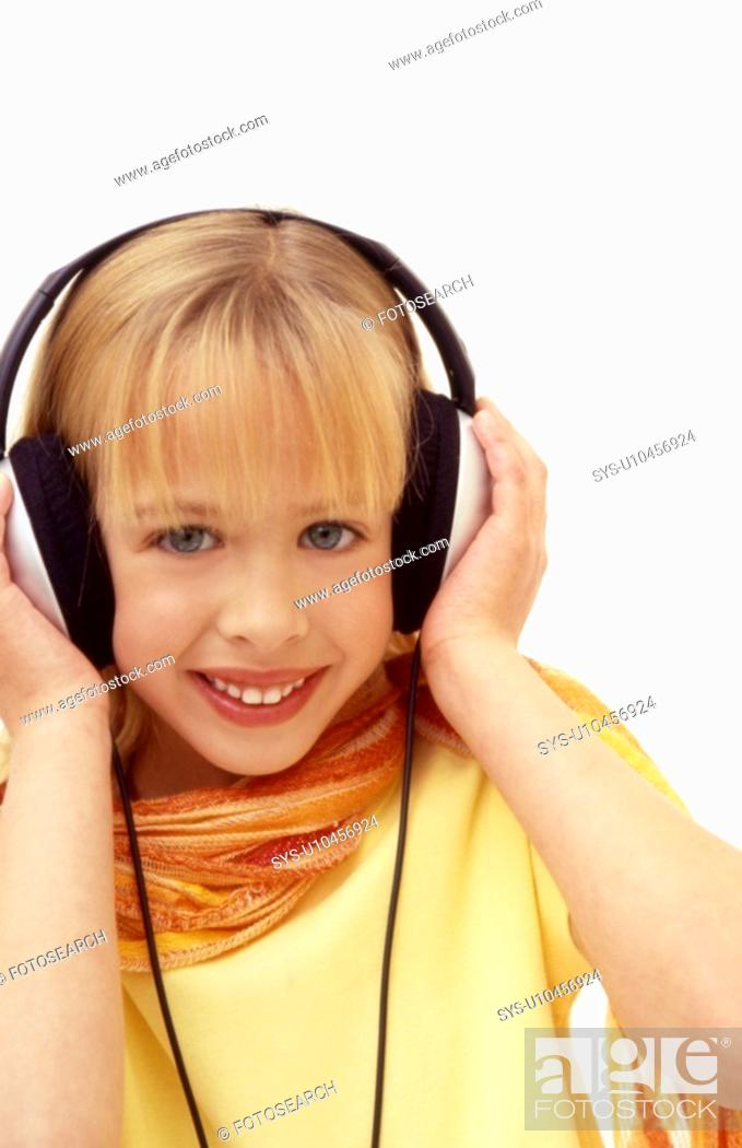 Stock Photo: A young girl listens to music with large earphones.