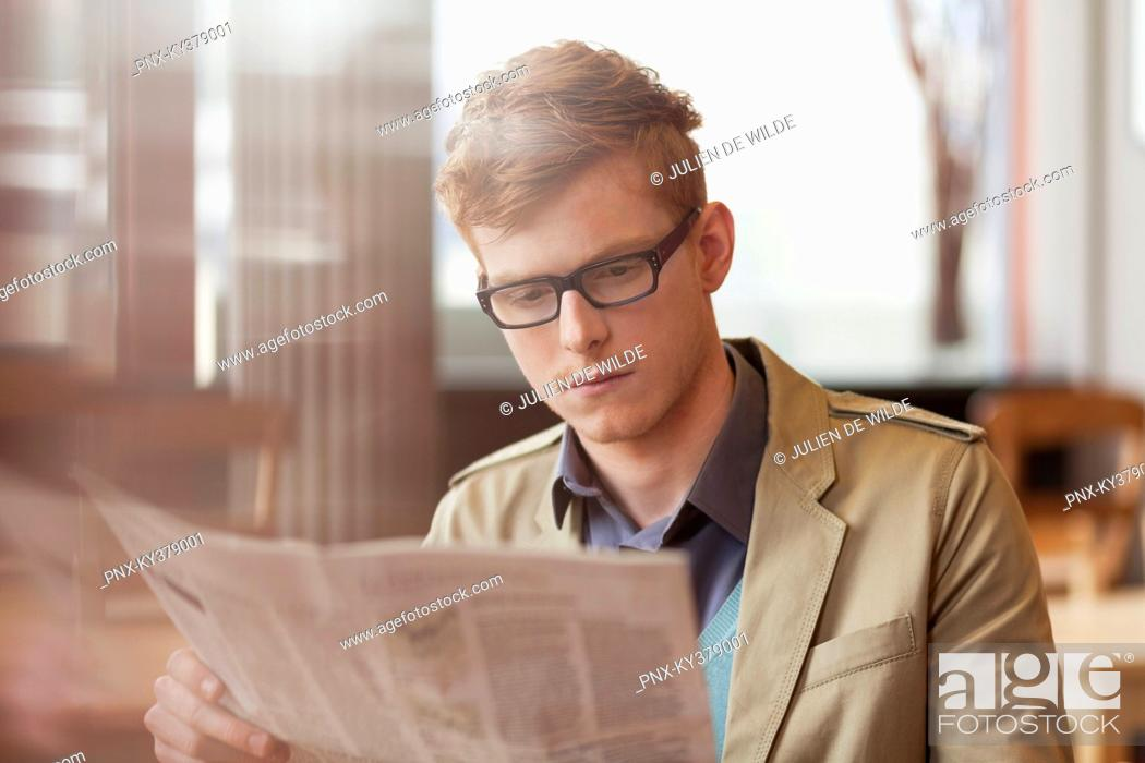 Stock Photo: Man reading a newspaper in a restaurant.