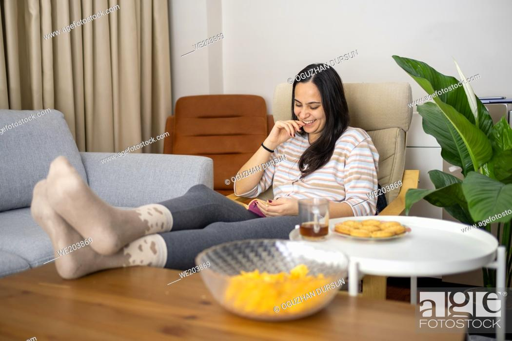 Stock Photo: one young lady sits on couch and laughs at something on book by extending her leg in living room with crisps, cookies and tea home interior copy space.