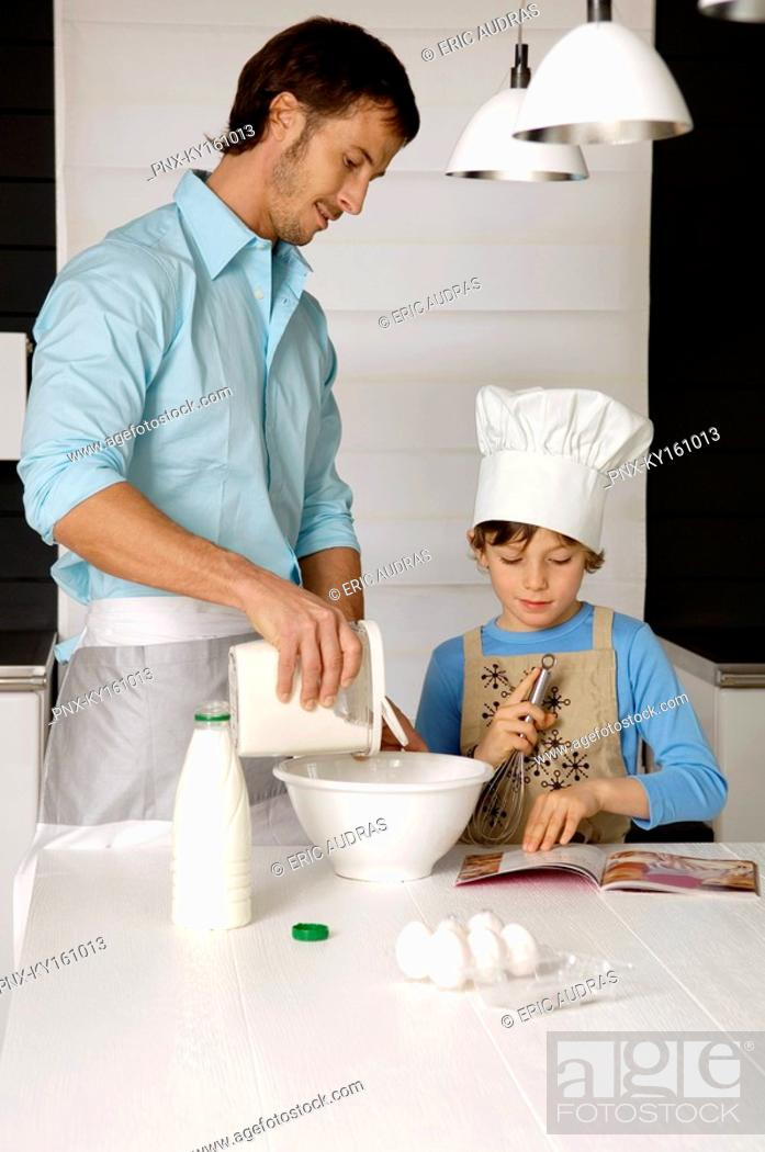 Stock Photo: Mid adult man making a cake with his son in the kitchen.