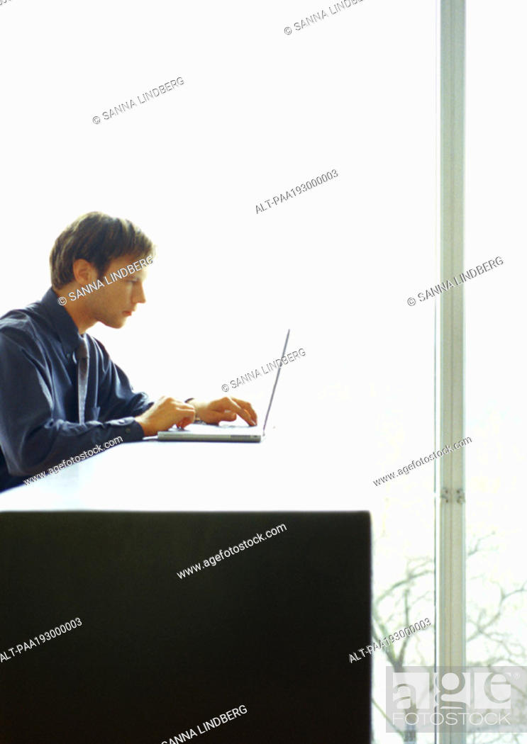 Stock Photo: Businessman sitting at desk working on computer.