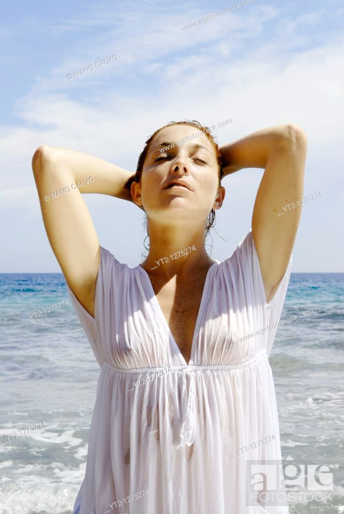 Stock Photo: Portrait of a cute and natural looking red haired girl posing on the beach, inside water, with a wet white dress, Ibiza, Spain.