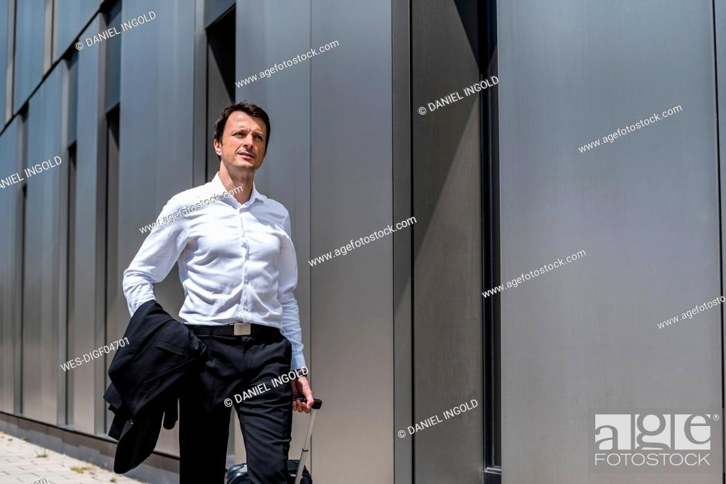 Stock Photo: Businessman with rolling suitcase walking in the city.
