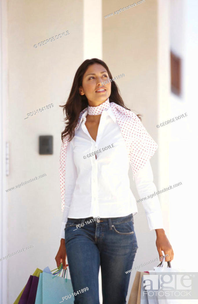 Stock Photo: young woman walking with shopping bags.