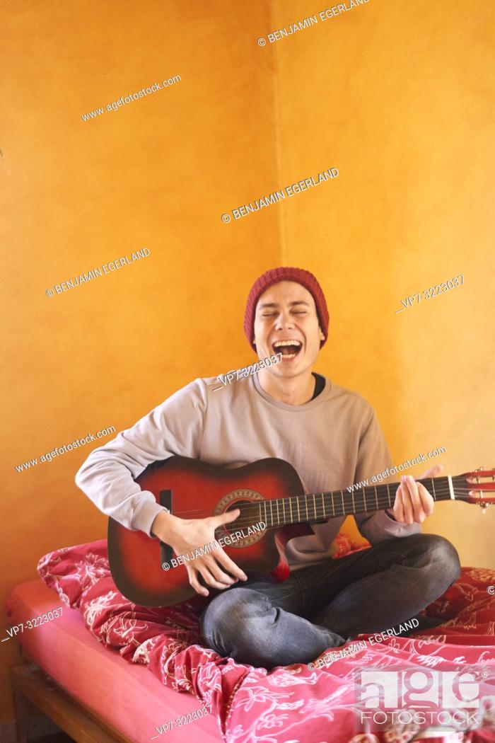 Imagen: young man playing guitar while sitting on bed, happy singing, lively, in Waakirchen, Bavaria, Germany.