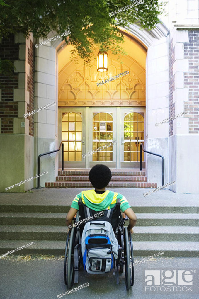 Stock Photo: Man in wheelchair looking at steps.