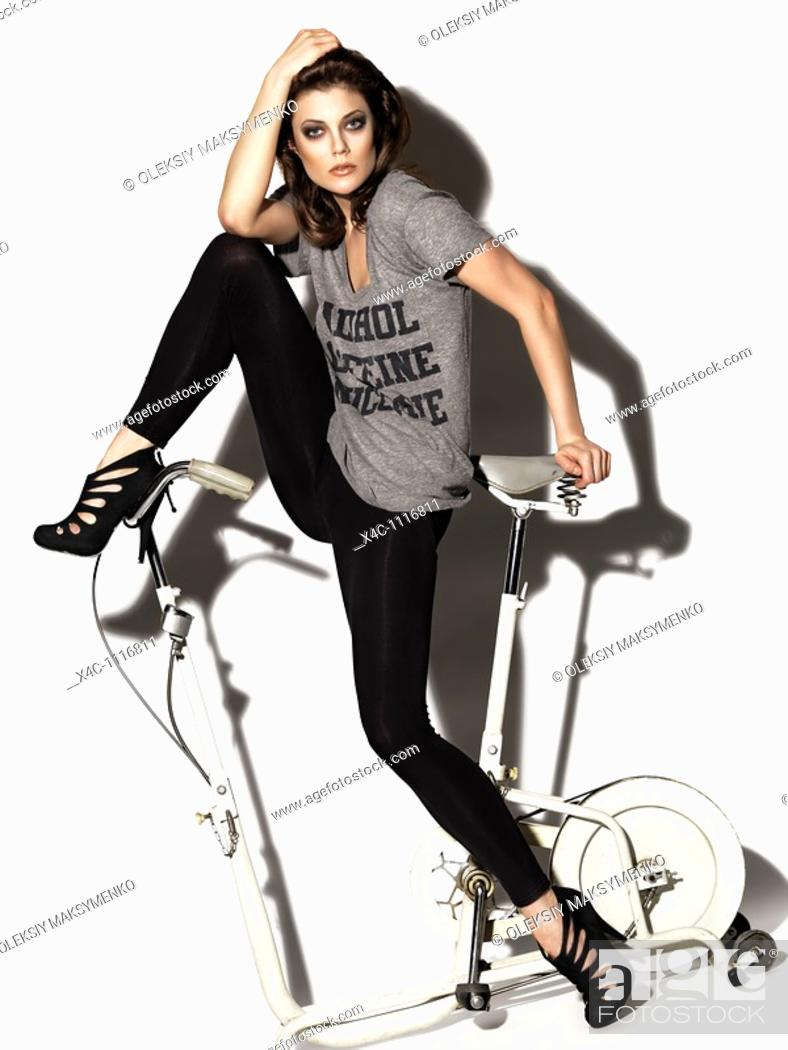Stock Photo: Young woman in a T-shirt and leggings posing on a retro exercise bike  Edgy high fashion photo.