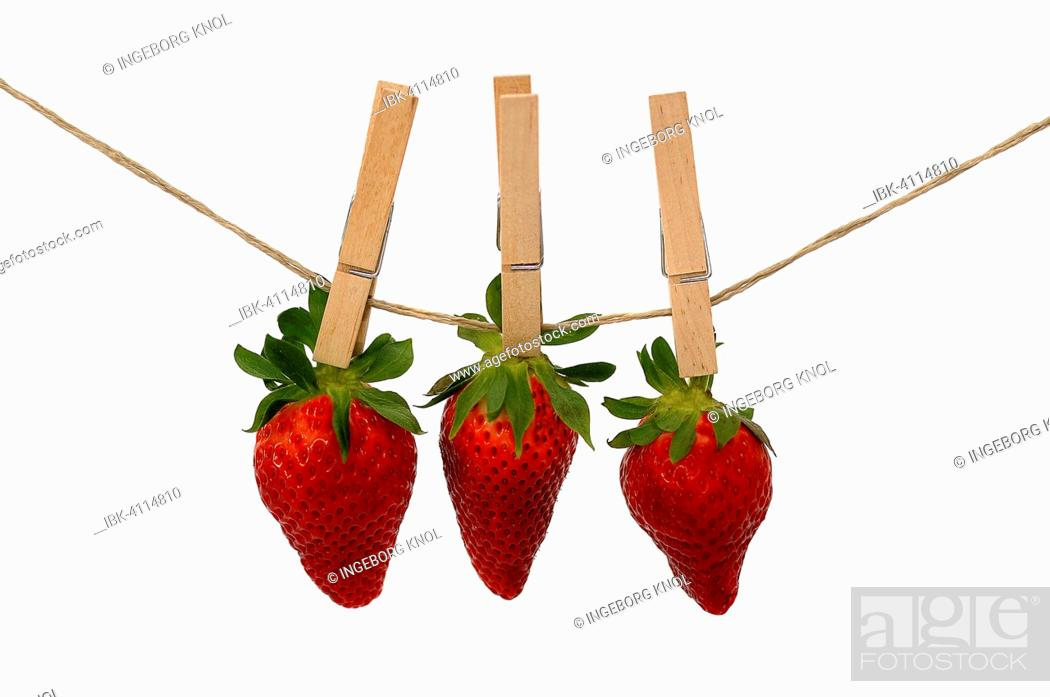 Stock Photo: Three strawberries with wooden clothespins on a line.