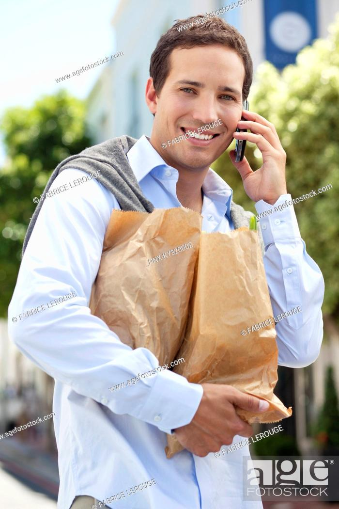 Stock Photo: Mid adult man talking on a mobile phone with paper bags full of vegetables.