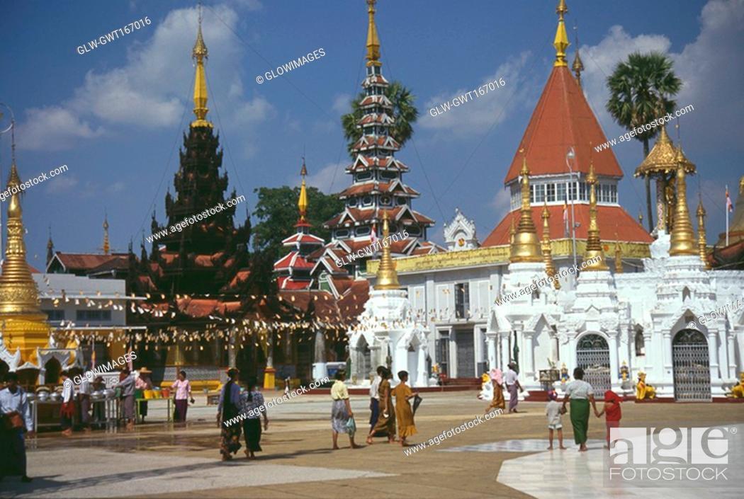 Stock Photo: Pilgrims walking in front of a pagoda, Shwedagon Pagoda, Yangon, Myanmar.