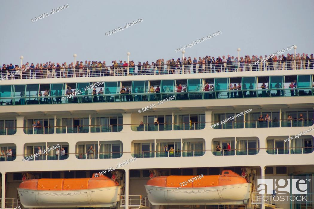 Stock Photo: Venice (Italy). Staterooms and tourists on an ocean liner next to the city of Venice.