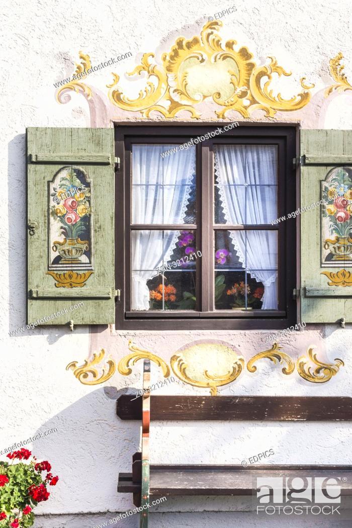 Imagen: bench under a window with wooden shutters painted with floral motifs, garmisch-partenkirchen, bavaria, germany.