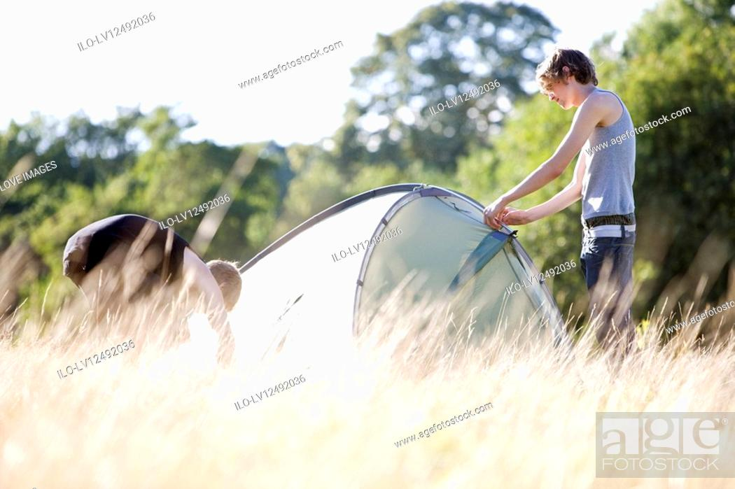 Stock Photo: Two young men setting up a tent in a field.