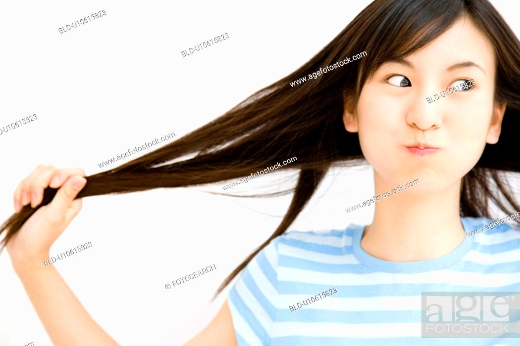 Stock Photo: Woman drawing her own hair.
