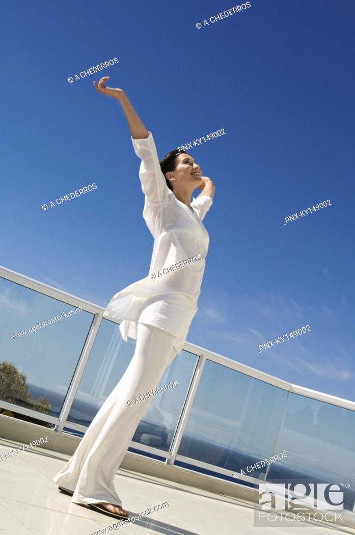 Stock Photo: Young woman stretching on terrace.