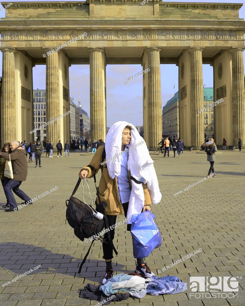 Imagen: young tourist man, traveller, carrying too much baggage, in front of touristic sight Brandenburg Gate, in Berlin, Germany.