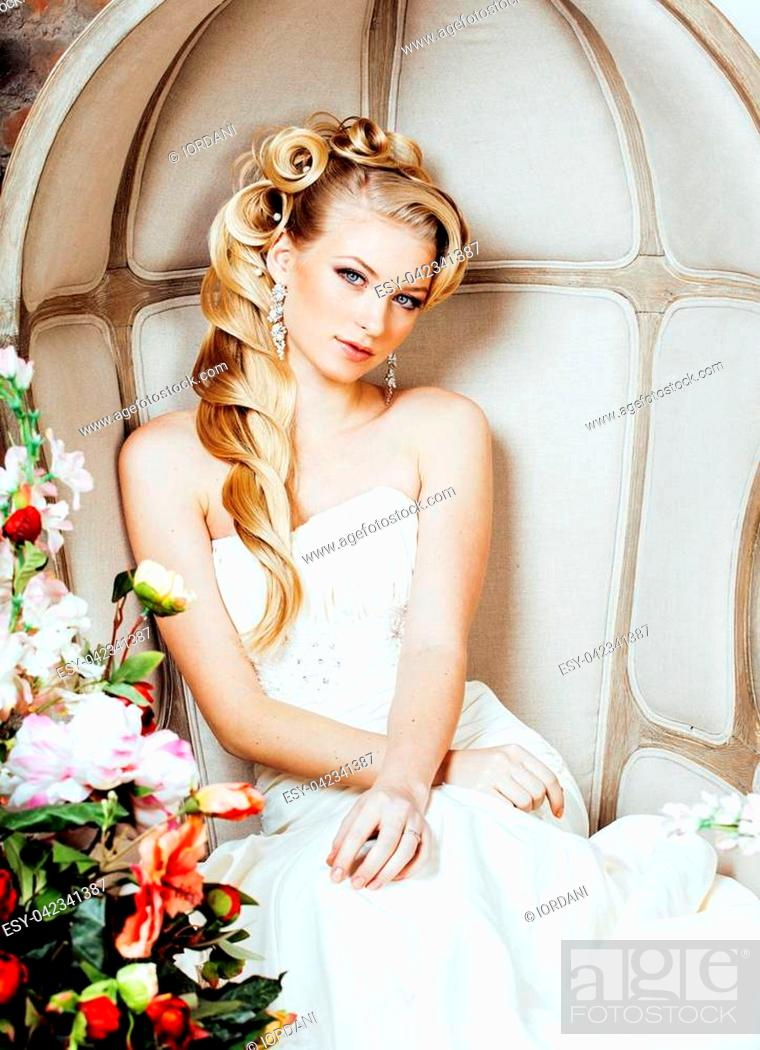 Imagen: beauty emotional blond bride in luxury interior dreaming, crazy complicate hairstyle, many flowers.