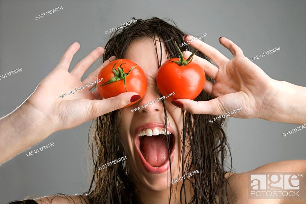 Stock Photo: Caucasian woman with tomatoes covering her eyes.