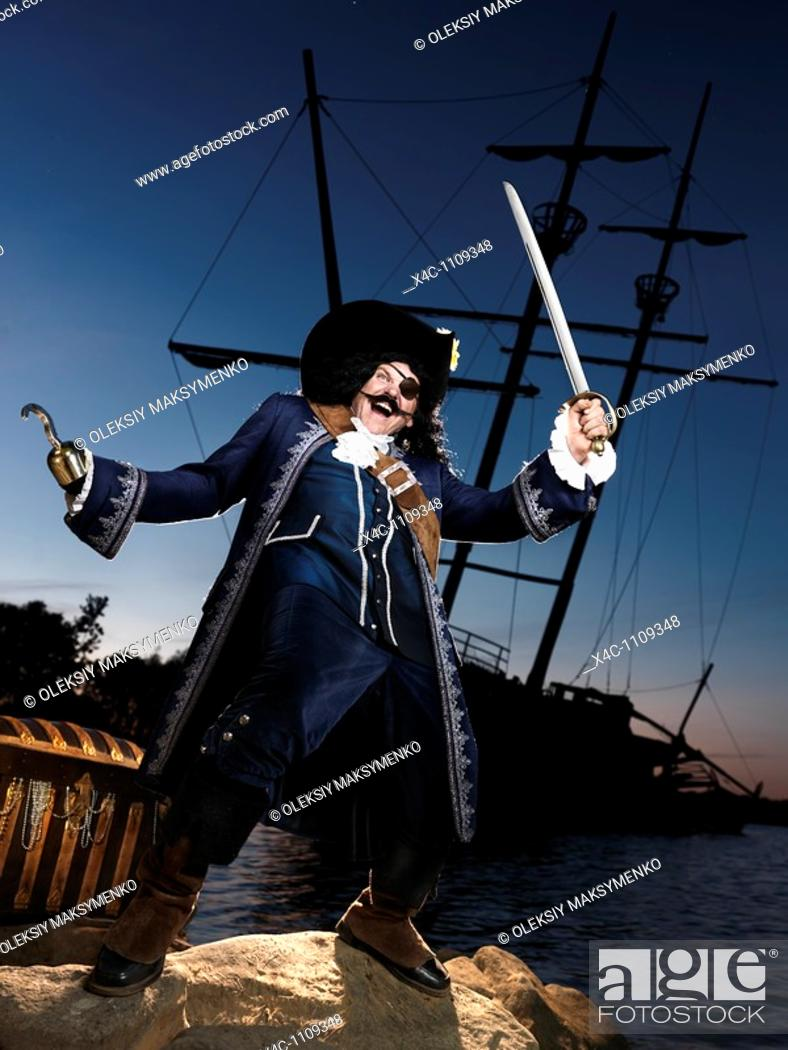 Stock Photo: Pirate ashore with a treasure chest and a wrecked old ship in the background.