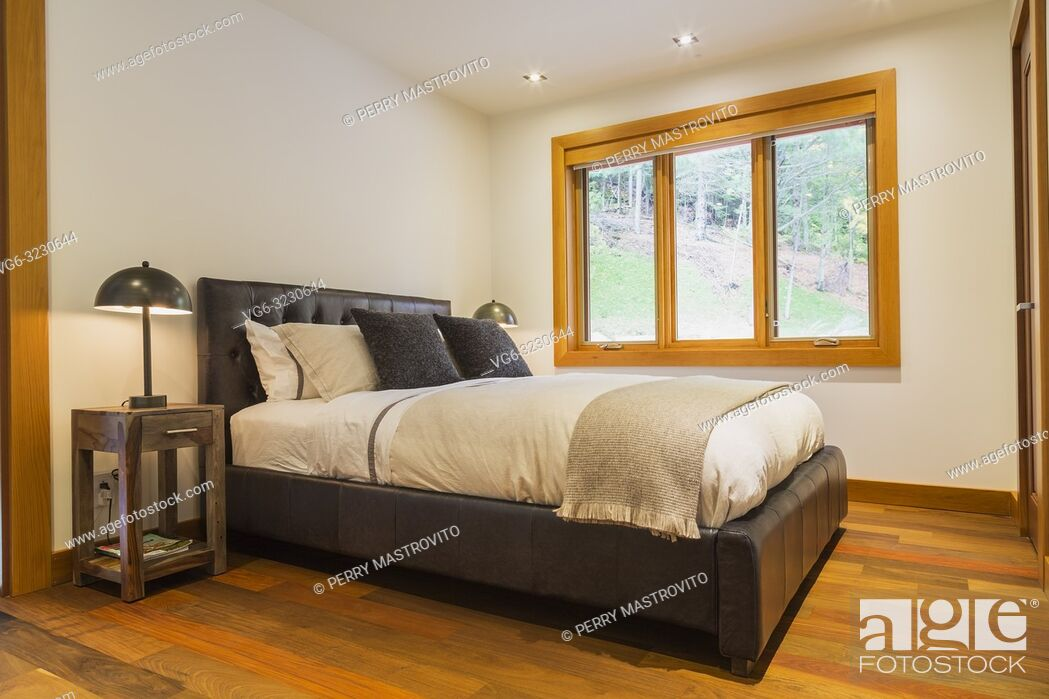 Stock Photo: King size bed with brown leather panel headboard and wooden end tables with illuminated lamps in guest bedroom with Ipe wood floor inside luxurious stained.