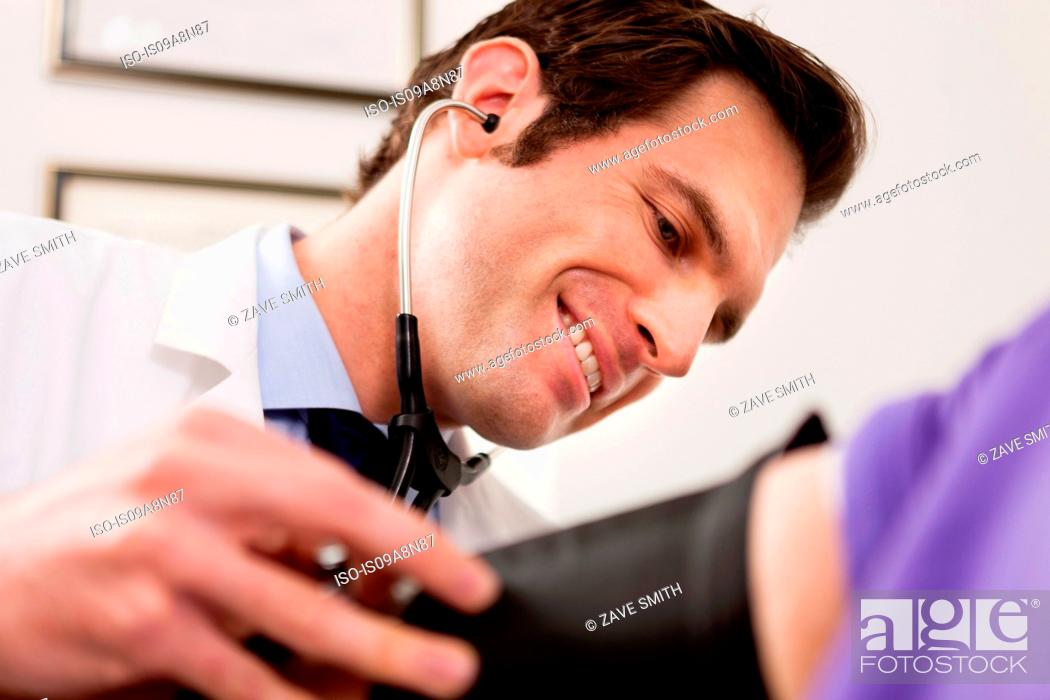 Stock Photo: Mid adult doctor using stethoscope and blood pressure cuff on patient, close up.