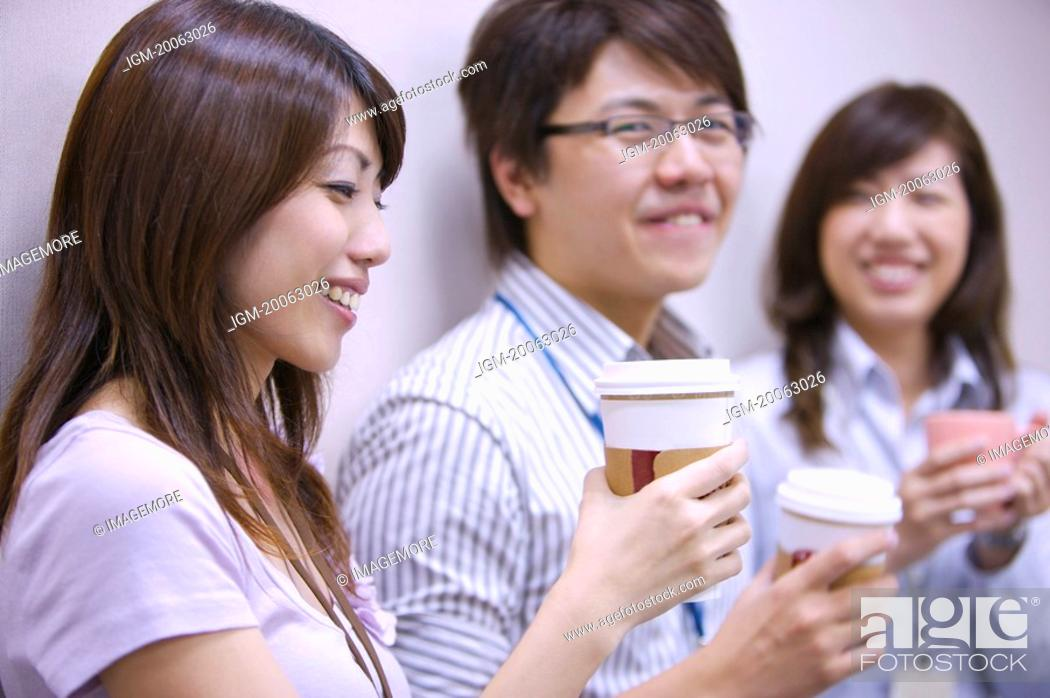 Stock Photo: Three colleagues holding coffee and smiling together.
