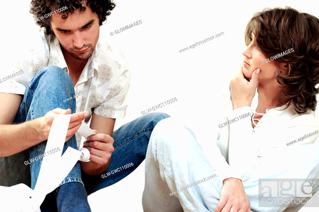 Stock Photo: Young man sitting with a young woman holding a receipt.