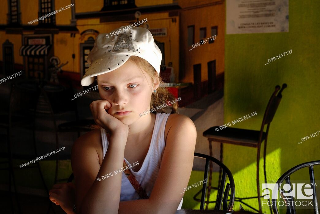 Stock Photo: Young girl with hat wating for fod at a restaurant, Nogales, Mexico.