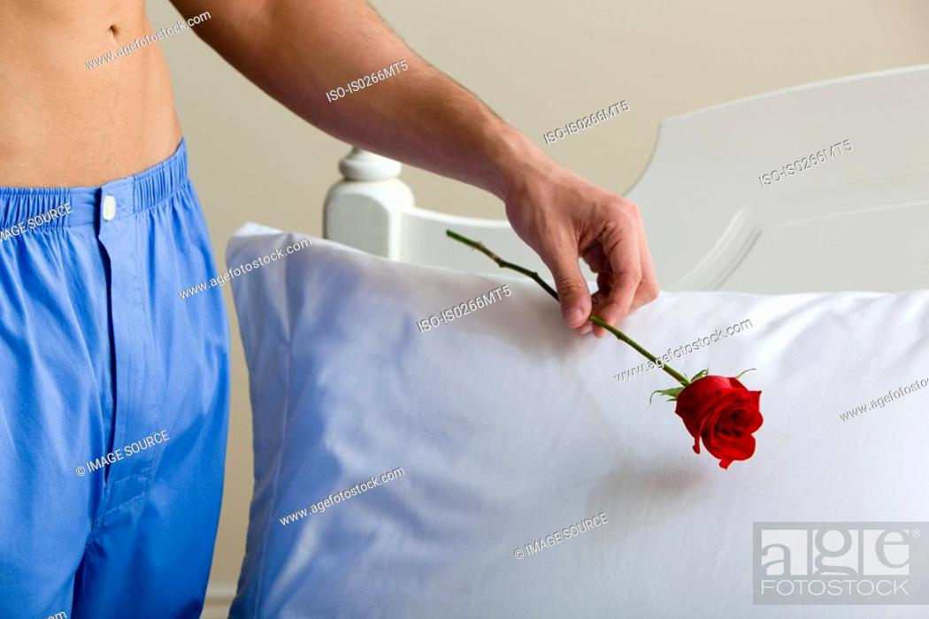 Stock Photo: A man putting a rose on a pillow.