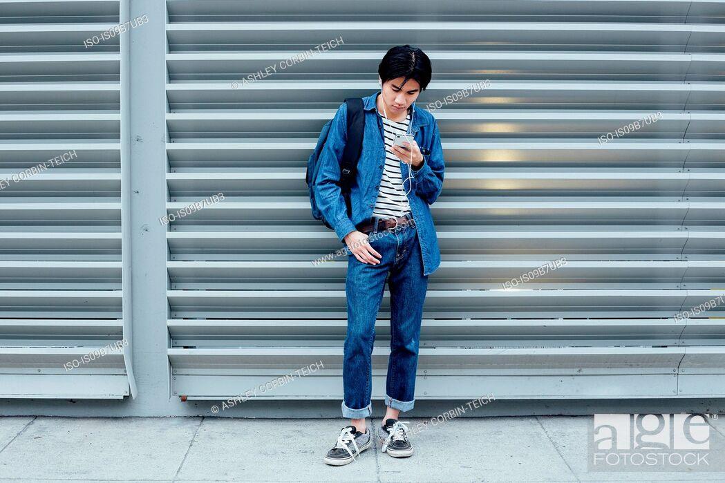 Stock Photo: Young man standing outside, using smartphone, wearing earphones.