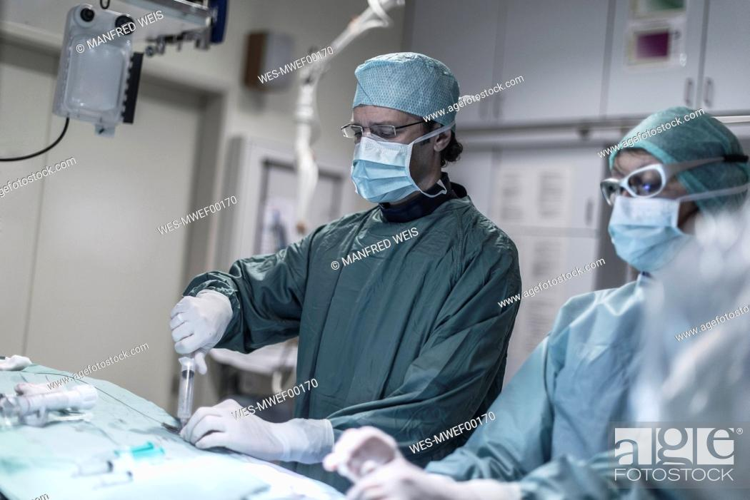 Stock Photo: Neuroradiologist with assistant using syringe during an operation.