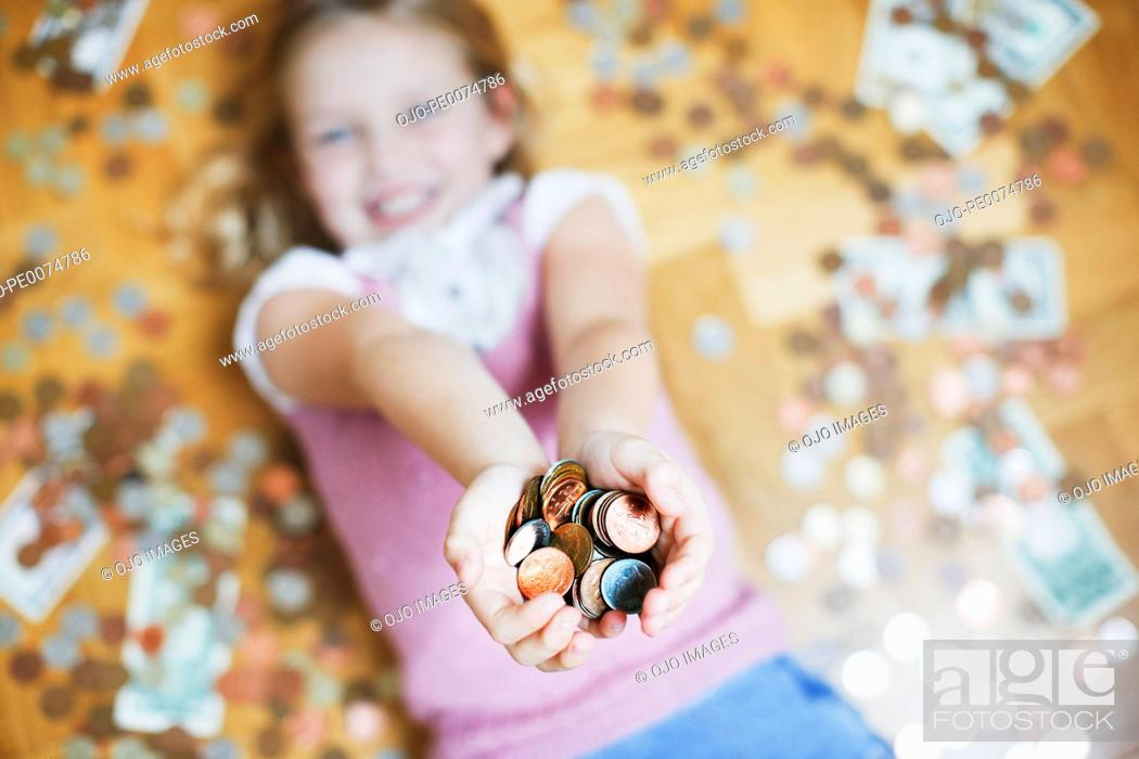 Photo de stock: Girl laying on floor holding handful of coins.