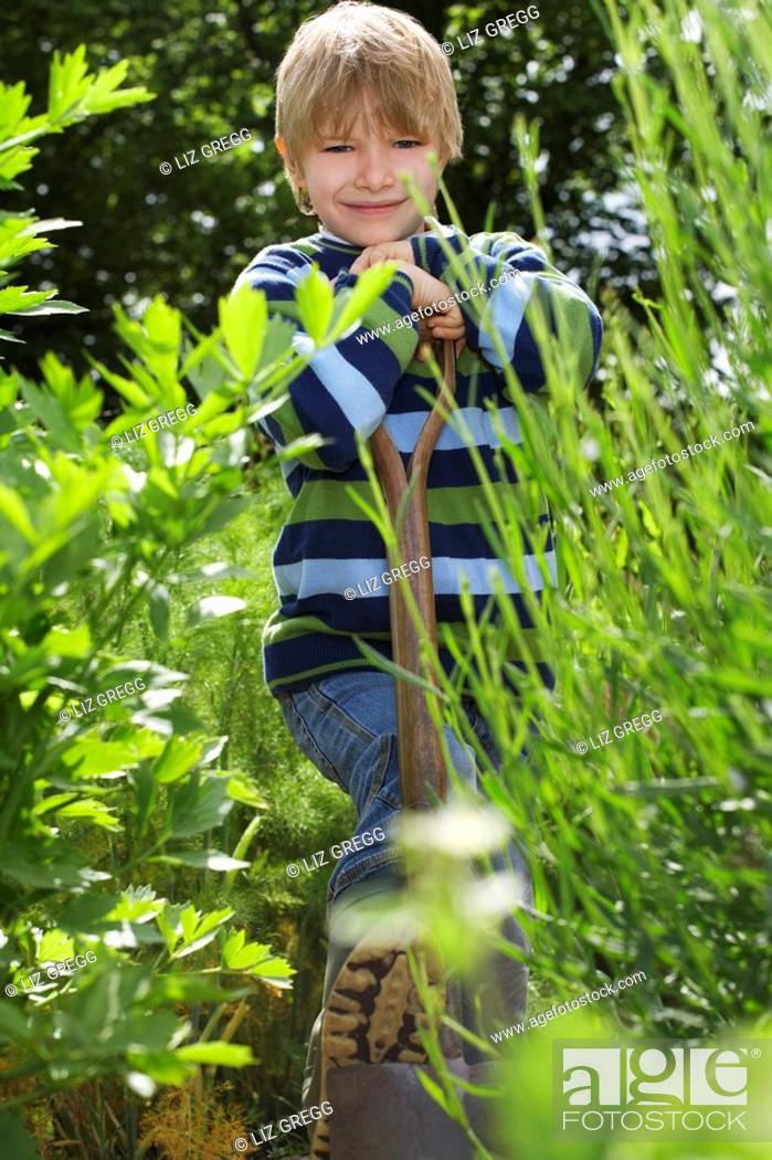 Stock Photo: Boy 5-6 with spade surrounded by plants portrait.