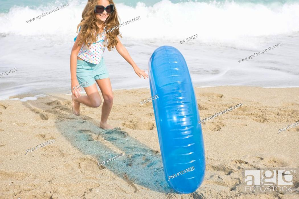 Stock Photo: Girl rolling an inflatable ring on the beach.