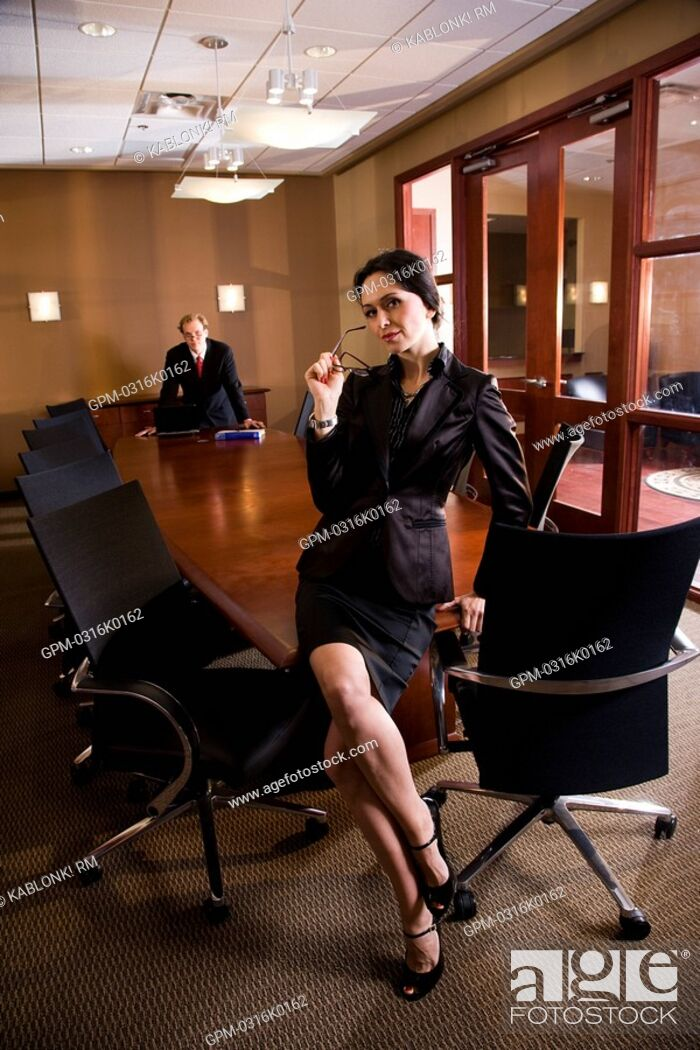 Stock Photo: Portrait of businessman and businesswoman in boardroom.