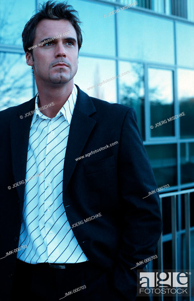 Stock Photo: A salesman, businessman, tradesman, employee, officer, young man standing in front of a modern office building.