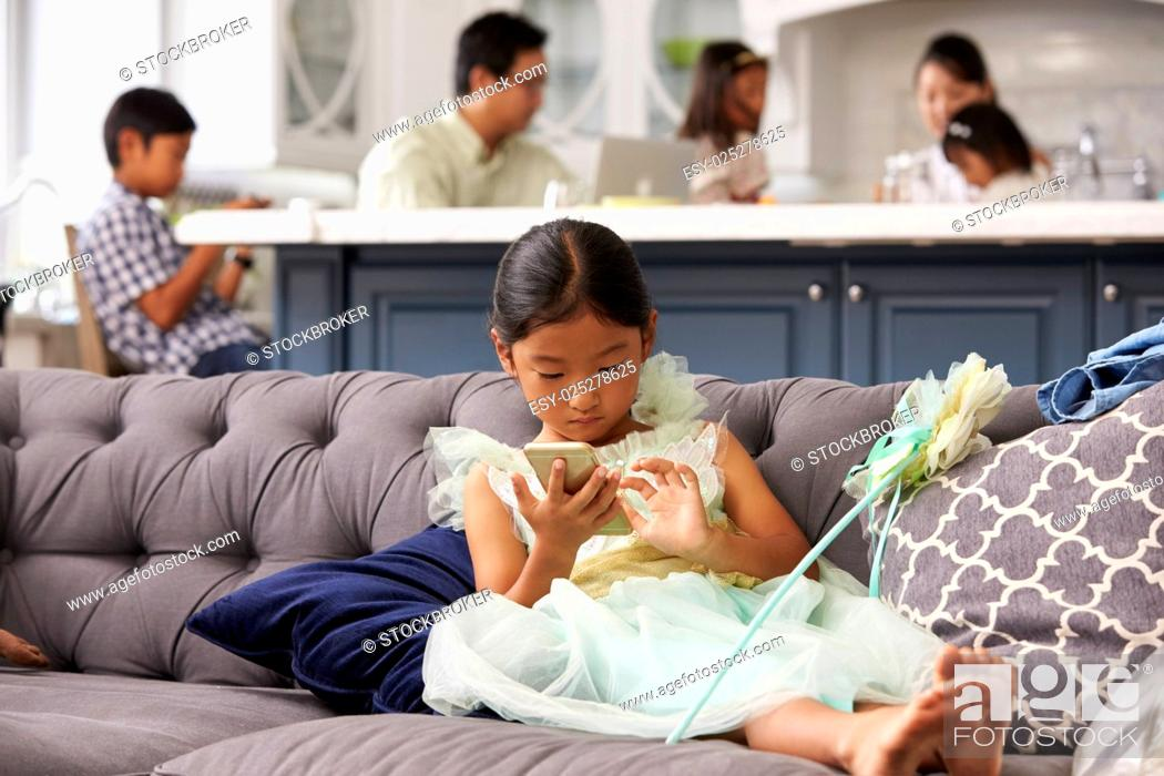Stock Photo: Young Girl Sitting On Sofa Using Mobile Phone At Home.
